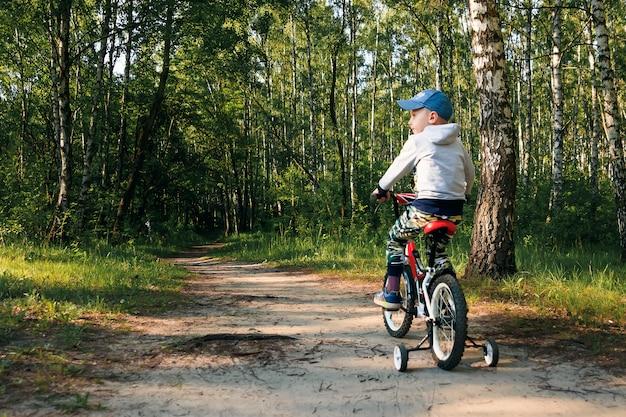 早朝の森の自転車の子。少年がヘルメットで屋外サイクリング