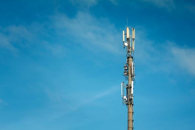 青い空と大きな白い雲に対して設定された通信マスト