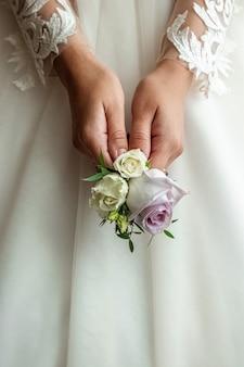 結婚式。花嫁の手でカラフルなバラのウェディングブーケ。