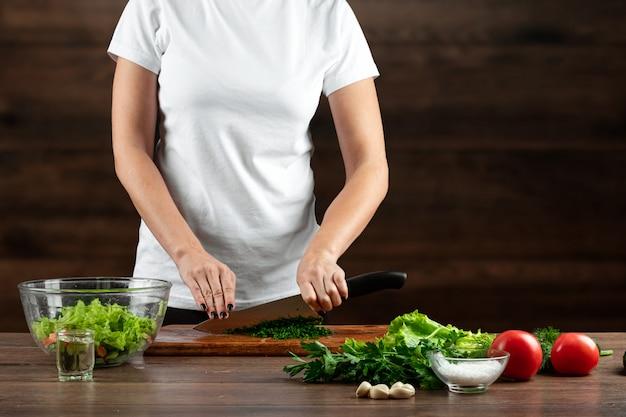 女性料理人は、木の上のサラダの準備のために野菜をカットします。