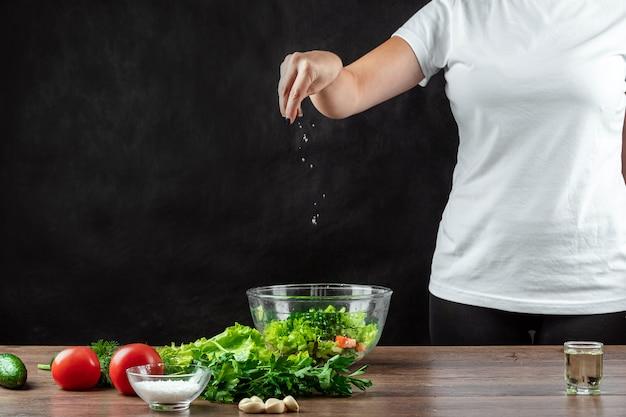 Женщина готовит соленые овощи, готовит салат по дереву.