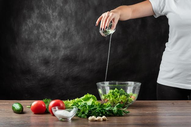 Женщина-повар добавляет в салат оливковое масло, готовит салат по дереву.