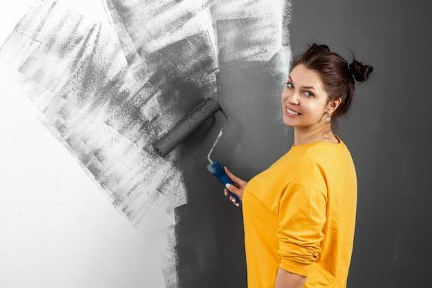 黄色いセーターの美しい少女は、灰色の塗料で壁を塗ります。部屋の塗装、修理、デザイン。コピースペース。
