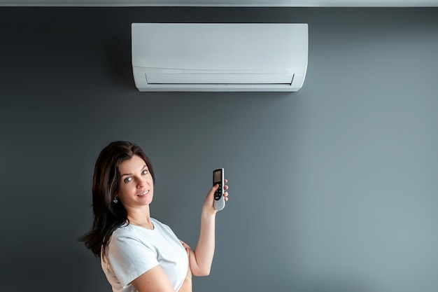 Красивая девушка стоит под кондиционером и потоком свежего холодного воздуха у серой стены. понятие тепла, прохладного воздуха, охлаждения, свежести.