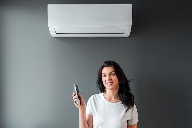 美しい少女は、エアコンと灰色の壁に新鮮な冷たい空気の流れの下に立っています。熱、冷気、冷却、鮮度の概念。