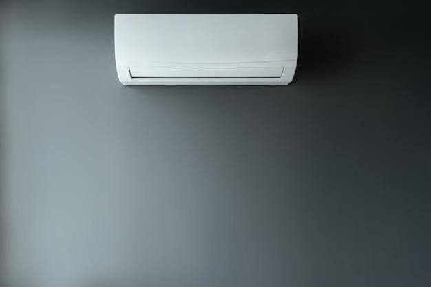 灰色の壁の背景に白いエアコン。熱、冷気、冷却、鮮度の概念。