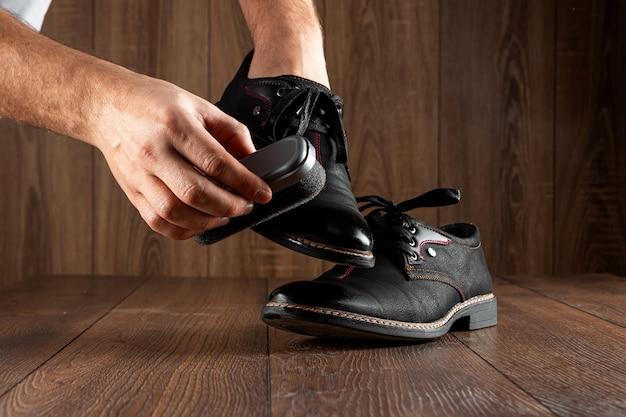 男性の手は木製の壁に黒い靴をきれいにします。靴の輝き、服のケア、サービスの概念。