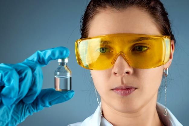 少女は医師、科学者、研究室助手であり、ワクチン、医療検査、実験室、実験のボトルを持っています。病気の治療の予防接種の化学分析。