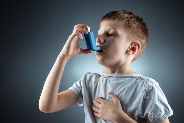 喘息吸入器を使用して炎症性疾患、息切れを治療する少年の肖像画。咳、アレルギー、気道疾患の治療の概念。
