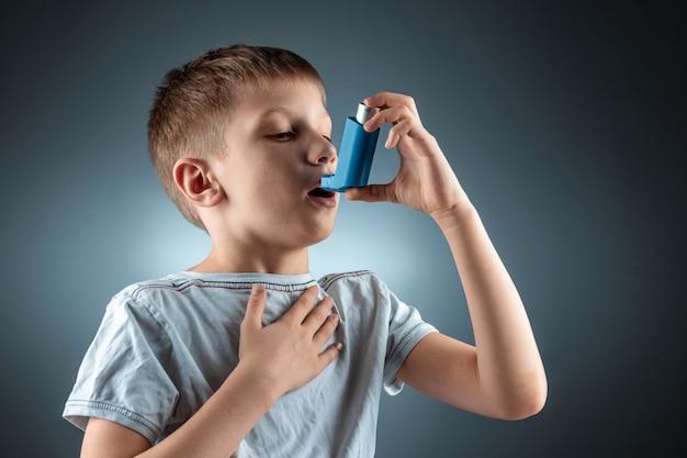 Портрет мальчика с помощью астмы ингалятор для лечения воспалительных заболеваний, одышка. концепция лечения кашля, аллергии, заболеваний дыхательных путей.