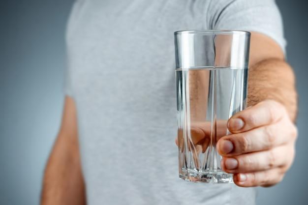 灰色の表面に男性の手のクローズアップで純粋なミネラルウォーターとガラスカップ。薬、治療、健康ドリンク。