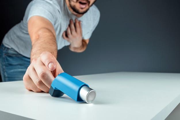 Мужская рука тянется к ингалятору астмы, приступу астмы. концепция лечения бронхиальной астмы, кашля, аллергии, одышки.