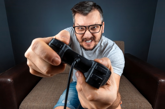 Мужчина играет на консоли, видеоигры реагируют сильно и эмоционально, сидя на диване. выходной, развлечения, отдых.