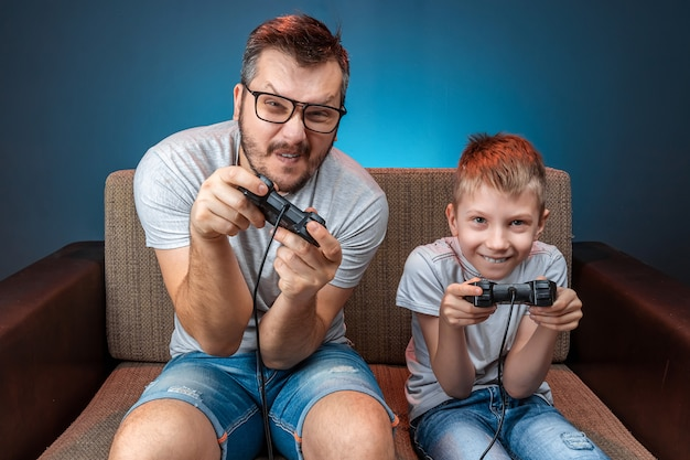 陽気な家族、父と息子は、コンソールで、ビデオゲームで、ソファに座って感情的に反応します。休日、エンターテイメント、レジャー、一緒に時間を過ごす。