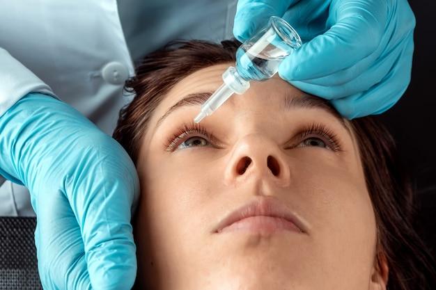眼科医は、眼科クリニックで患者の目に滴を注入します。健康、視力、眼疾患。