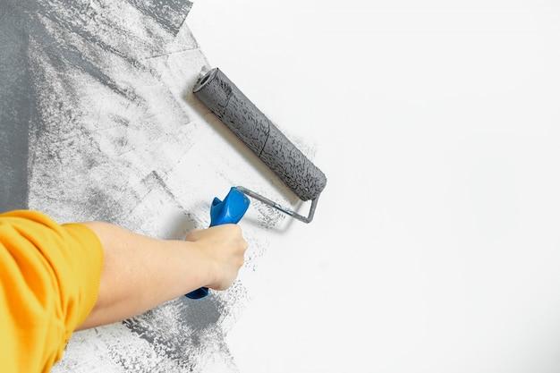 女性の手のクローズアップは、灰色で壁をペイントします。修理、変更、デザイン、背景の概念
