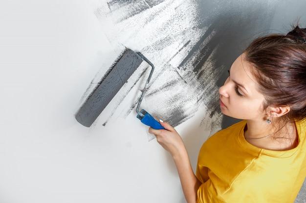 美しい少女は、ローラー、灰色の塗料で黄色のジャケットの壁をペイントします。修理、変更、デザイン、インテリアの概念。