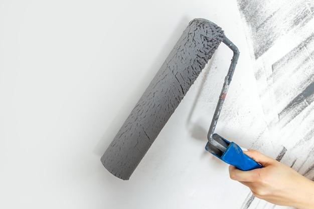 女性の手のクローズアップは、灰色で壁をペイントします。修理、変更、設計の概念