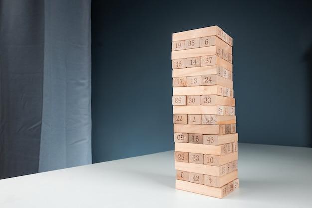 列ゲームジェンガ。住宅ローン、投資リスク、経済危機、経済不安定の背景の概念