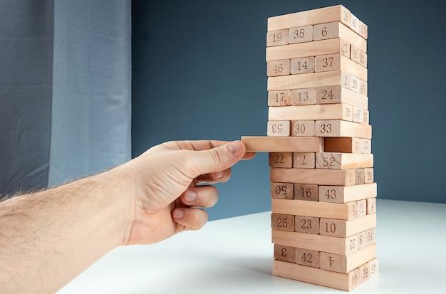 列ゲームジェンガ。住宅ローン、投資リスク、経済危機、経済不安定の概念。