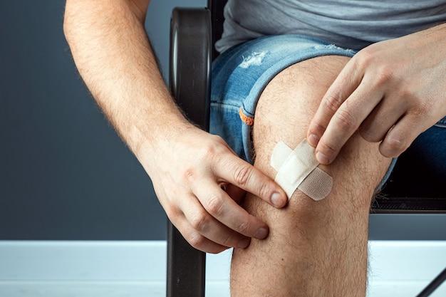 男は、絆創膏のクローズアップで膝の傷を封印します。救急車、ボディケア、膝の怪我。
