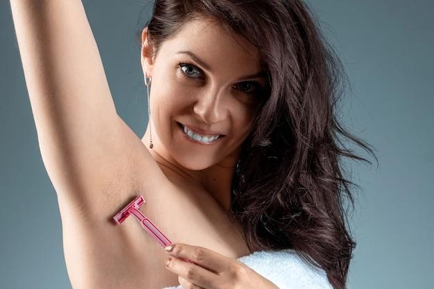 若い女の子、彼女の手を上げると彼女の脇の下を剃る