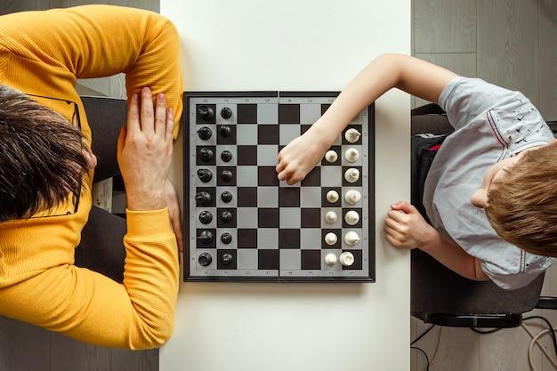 Мальчик с отцом играет в шахматы
