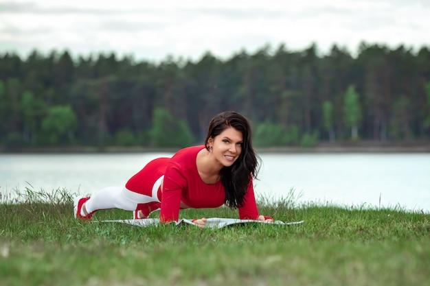 Девушка в спортивном костюме делает штангу, физические упражнения на прессе на фоне природы. концепция здорового образа жизни, упражнения, свежий воздух. копировать пространство