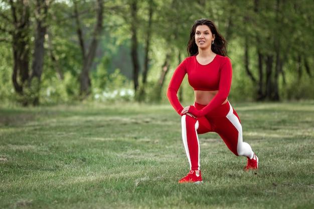 Красивая девушка в спортивном костюме делает растяжку перед спортивными упражнениями на природе, на свежем воздухе. концепция здорового образа жизни, фитнес. копировать пространство