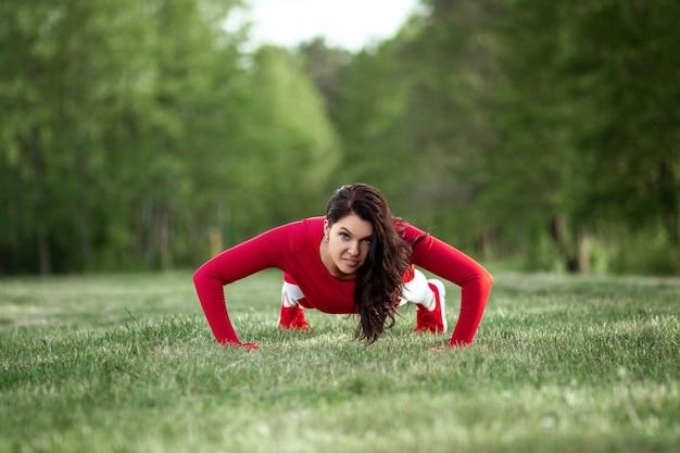 Девушка в спортивном костюме делает отжимания, делает физические упражнения на фоне природы. концепция здорового образа жизни, упражнения, свежий воздух. копировать пространство