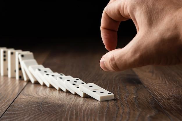 Мужская рука толкает белые домино