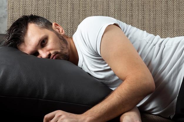 白いシャツを着た男がソファに横になっています。