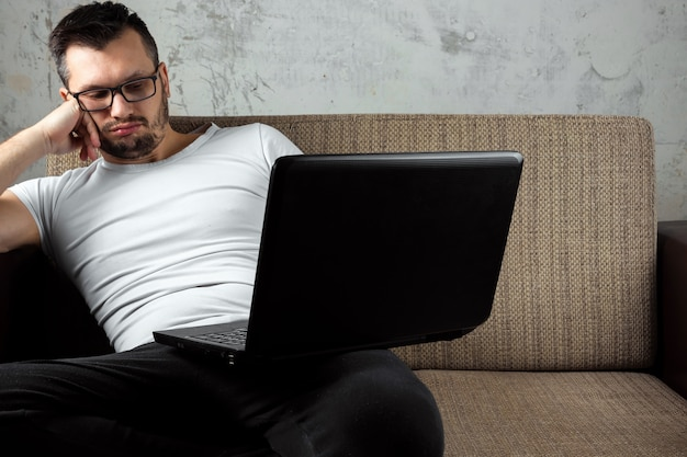 ソファの上に座っている白いシャツを着た男が、ラップトップで仕事で眠りに落ちた。
