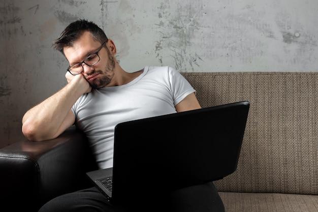 Парень, одетый в белую рубашку, сидя на диване, уснул за работой на ноутбуке.