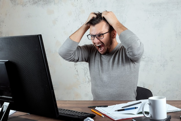 Возмущенный человек, человек, сидящий за столом в кабинете и кричащий в гневе