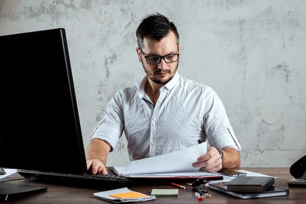 男は、重要な論文に取り組んでいる、オフィスのテーブルに座っています。事務のコンセプトです。スペースをコピーします。