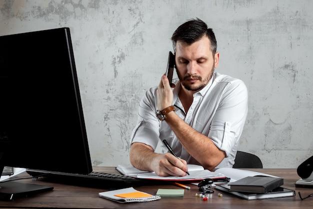 電話で話して、オフィスのテーブルに座っている男は、重要な質問を決定します。