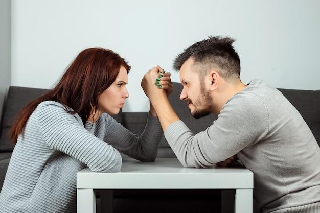 夫と妻は彼らの腕の中で戦っています、男性と女性の間の腕相撲。家族の口論、対決、財産の分割、離婚。女性と男性の間の闘争。