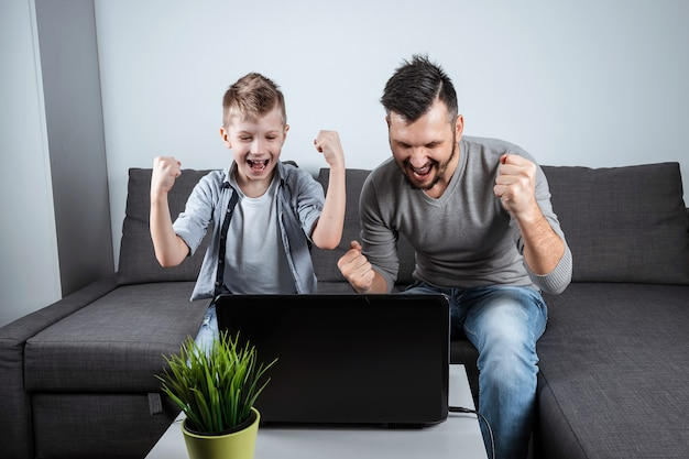 Отец и сын смотрят футбол в ноутбуке дома