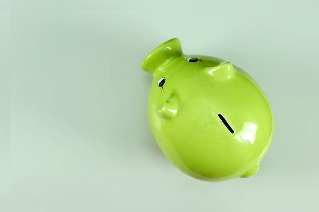 灰色の背景の上面に緑の豚貯金箱