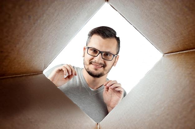 Распаковывая, мужчина открывает коробку и заглядывает внутрь