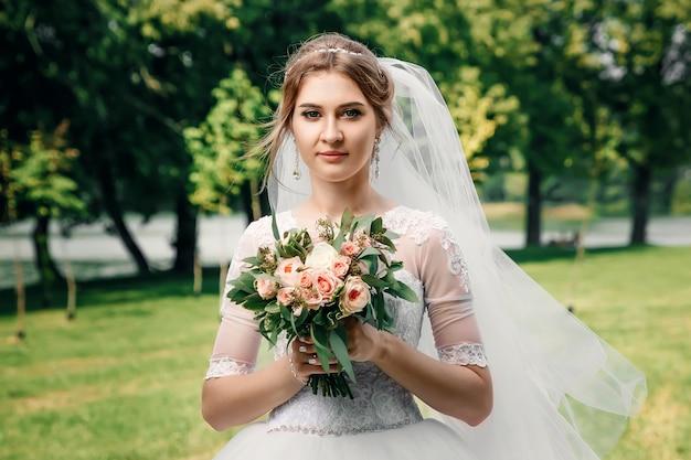 美しい少女、緑の自然の背景に白いウェディングドレスの花嫁。結婚式、家族の創造。