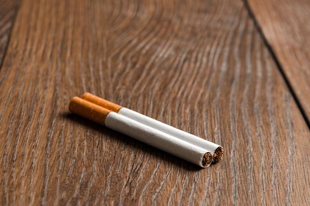 木製の茶色の背景にタバコのクローズアップ。