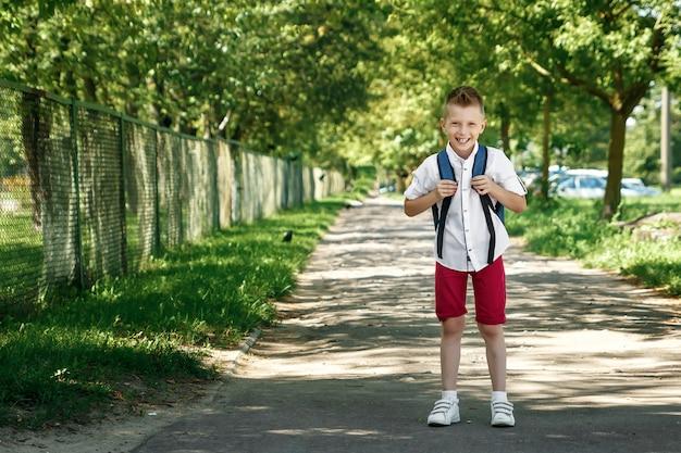路上でバックパックを持った小学校の少年