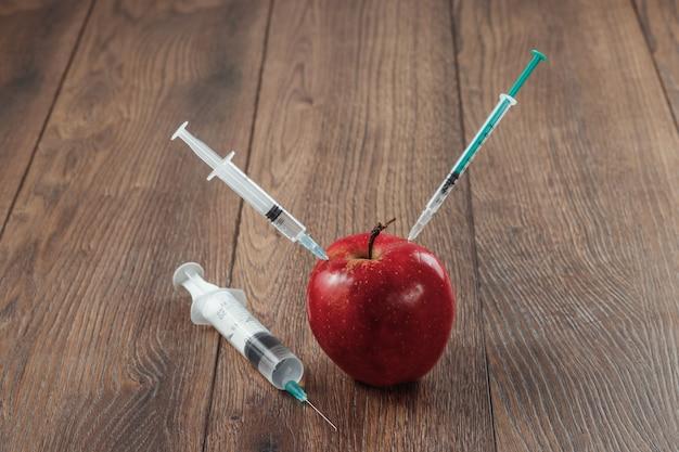 木製の背景に針または注射器と化学農薬を注入する赤いリンゴ