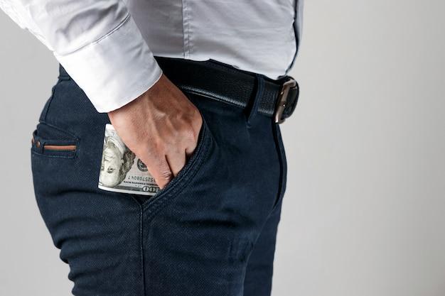 彼のズボンのポケットにお金を持つ男