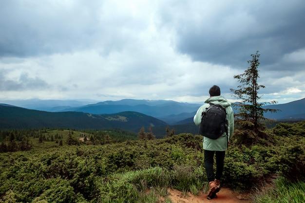 男性観光客がバックパックで山岳地帯を歩く