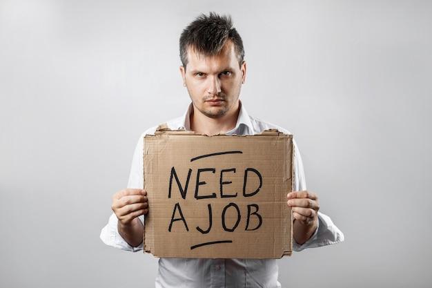 碑文と段ボールを保持している男は仕事が必要です