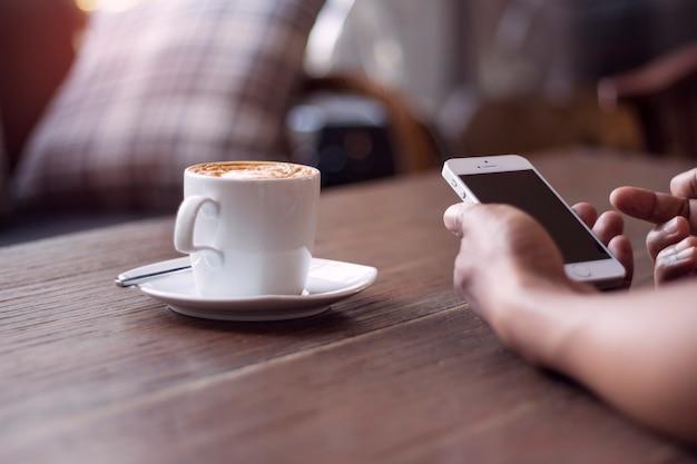 スマートフォンをテーブルの上で作業する人