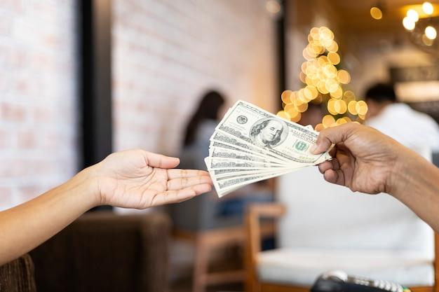 Человеческие руки обменивают долларовые деньги